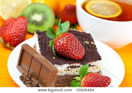 Lemon Tea,chocolate, Kiwi,cake And Strawberries Lying On The Orange Fabric