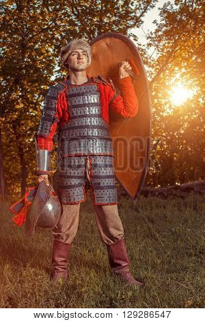 Brave Slavic Warrior With Shield On The Summer Forest Background.