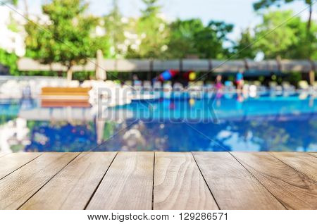 Wooden table on blur pool background with beach chairs