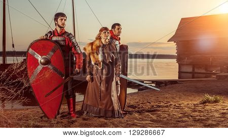 Slavic Princess And Two Warriors With Swords And Shields On The Warships Background.