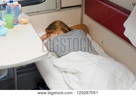 The Girl In A Train Sleeping On His Stomach With His Hands Behind His Head On The Lower Second-class