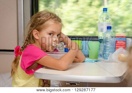 A Six-year Girl In A Train Sitting At The Table On The Lower Place In The Second-class Compartment O