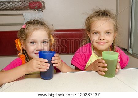 Two Girls Sisters On The Train Sitting At The Table On The Lower Place In The Second-class Compartme