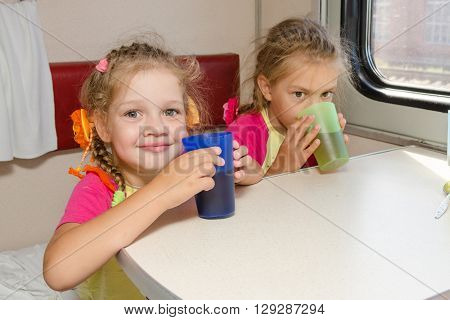 Two Little Sisters In A Train Drinking Tea At A Table On The Lower Place In The Second-class Compart