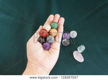 Colourful round stones in hand, quartz gem