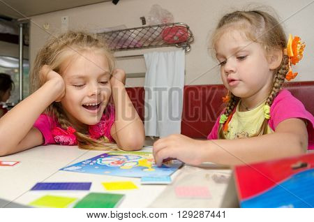 Two Girls Having Fun Playing On The Train At The Table On The Lower Place In The Second-class Compar