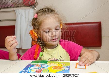 Little Girl On The Train Sits At A Table On The Lower Second-class Place Car And Enthusiastically Sk