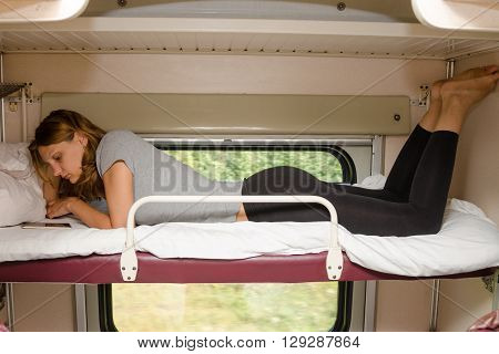 The Girl On The Train Lying On His Stomach On The Top Shelf In A Second-class Carriage And Looking A