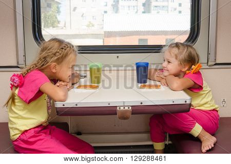 Two Little Girls With A Happy Face Looking At Each Other On The Train Sitting At The Table On Outboa