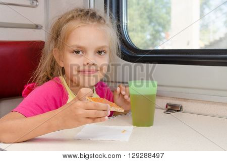 Six-year Girl Drinking Tea With A Sandwich On The Train At The Table On Outboard Second-class Carria