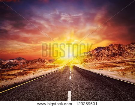 Travel forward concept background - vintage retro effect filtered hipster style image of road in Himalayas with mountains and dramatic clouds on sunset. Ladakh, Jammu and Kashmir, India