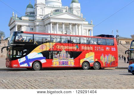 HELSINKI, FINLAND - MAY 10, 2016: Red double-decker Hop on Hop off sightseeing bus departs from Senate Square by Helsinki Cathedral. The visitor can hop on and off at any of the 15 main tourist attractions.
