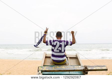 football fan sitting in a boat, with number 21 on the back