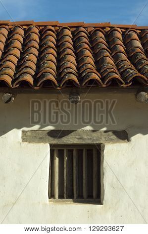 a picture of an exterior 1840's adobe building wall with window