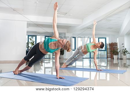 Two young women training in yoga asana in the sport gym