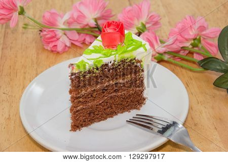 Cream cake with rose on the wooden table
