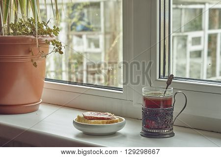 Composition with flower sandwich glass of tea and glass holder near window