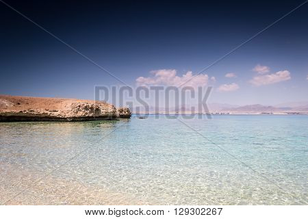 Horizontal photo with the sandy beach with calm clear sea deep blue sky and part of the island
