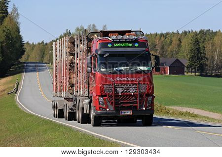 SALO, FINLAND - MAY 8, 2016: Red Volvo FH16 600 logging truck transports timber logs along rural road on a sunny day of spring in south of Finland.
