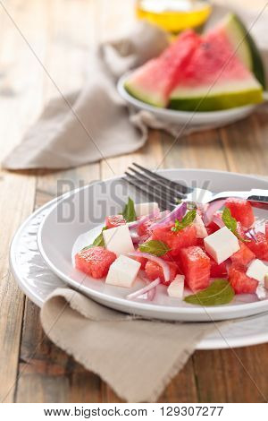 Watermelon salad with feta mint and red onion. On wooden rustic table.