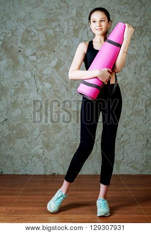 beautiful smiling teenage girl wearing sports clothes with a yoga mat