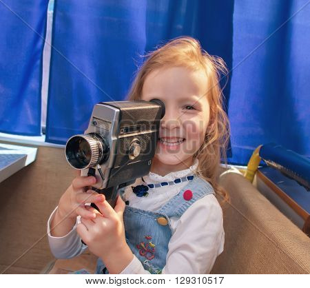 Portrait of a beautiful and confident small girl with camera. Little girl making a film in the camera.
