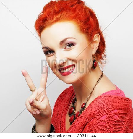 Happy smiling beautiful young woman showing two fingers or victory gesture