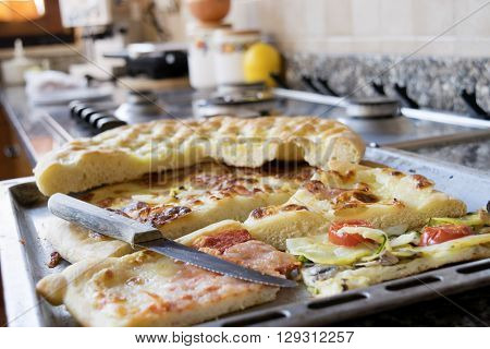 assortment of scraps of pizza in a baking tray on a hob