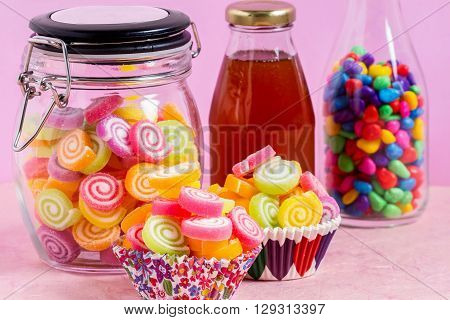 colorful candy with honey in jar on table on pink background