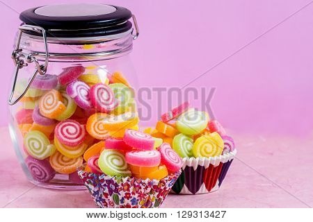Candy In Jar On Table On Pink Background