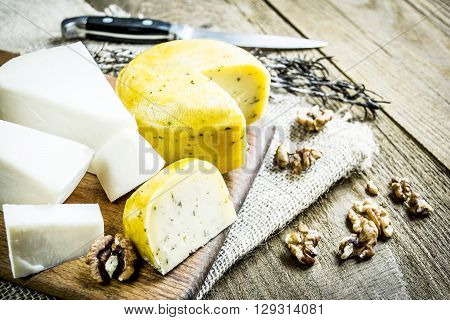 Two varieties of cheese  pieces on board on sacking rough on the table near the village of nuts against a background of rosemary and knife