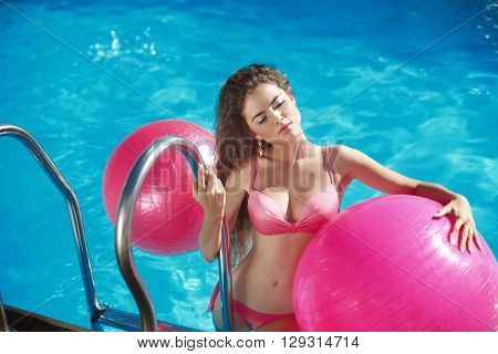 Beautiful Sexy Female Model With Pilates Fitballs Posing In Swimming Pool, Outdoor Summer Portrait.