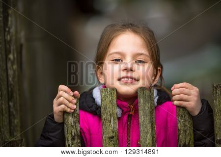 Portrait of little girl peeking from behind the fence.