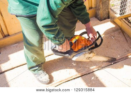 worker with chainsaw sawing boards. carpenter with a power saw running outdoors