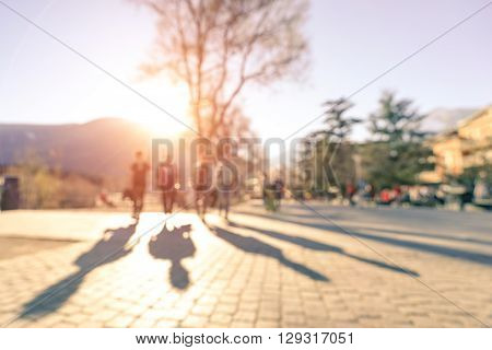 Blurred defocused silhouettes of four people walking on Meran streets at sunset - Wanderlust emotional youth concept with friends traveling together - Warm filter with rose quartz enhanced sunshine