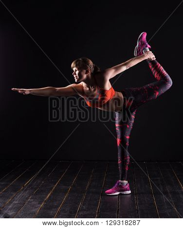 Beautiful young and fit fitness sport model doing yoga in dark studio.