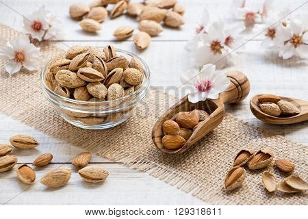 Diagonally on burlap napkin left glass bowl of almonds right almonds in wooden spoon behind and in front almond nuts flowers on light wooden background. Horizontal. Daylight. Close.