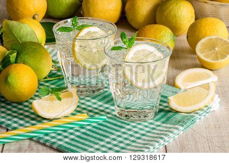 2 glasses of soda water with a slice of lemon mint leaves and ice cubes on a green checkered napkin behind scattered lemons on a light wooden background. Horizontal. Daylight.