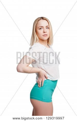 Pretty young woman wearing green shorts and striped tshirt posing isolated on white background