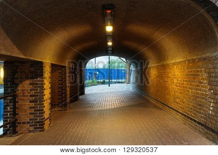 London urban underground brick tunnel with lights next to Albion Channel