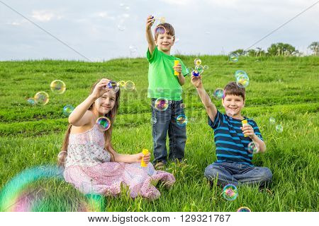 Three kids blowing up the soap bubbles on green lawn