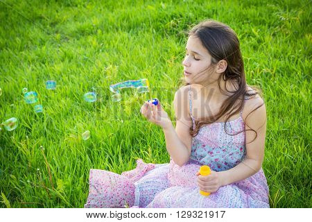 Girl blowing up the soap bubbles sitting on green lawn