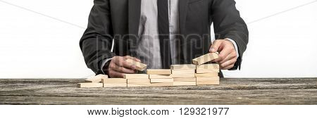 Front view of businessman arranging wooden pegs into a staircase like structure. Conceptual of business vision and determination.
