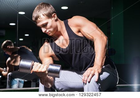 Young bodybuilder doing exercise on biceps with dumbbell