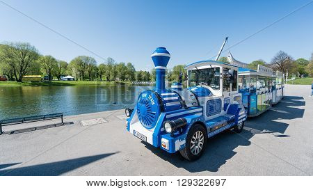 Munich, Germany, 24 April 2016: Tour train vehicle from Olympic Park in Munich, Germany. The Olympiapark in Munich, Germany, is an Olympic Park which was constructed for the 1972 Summer Olympics.