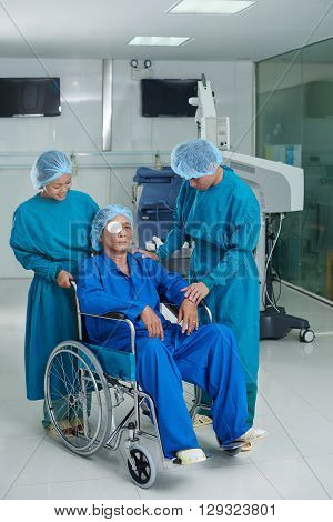 Surgeon, his assistant and senior patient in wheelchair after surgery