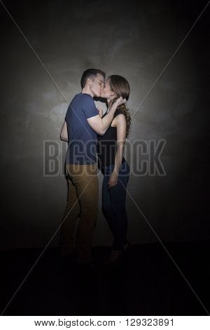 Young couple embracing and kissing on the dark gray background