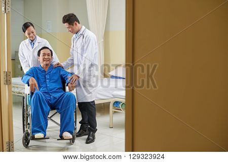 Happy mature Vietnamese man in wheelchair after operation