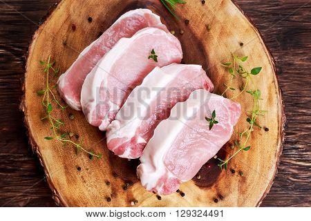 Raw Fresh Boneless Pork Chops with herbs. on wooden board..