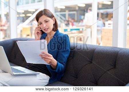 Young businesswoman sitting on a couch and talking on her mobile phone while looking at paperwork